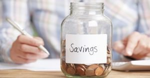 Woman Calculating Budget With Savings Jar In Foreground 1